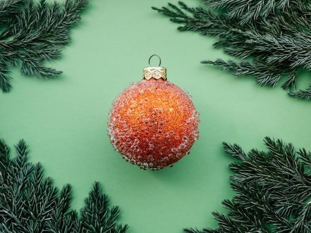 Czerwona bombka z kilkoma guzkami i świerkową gałązką na zielonym tle minimalistyczny świąteczny wzór