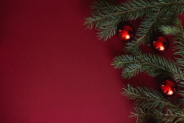 Czerwona bożenarodzeniowa baubles dekoracja na czerwonym tle z copyspace.