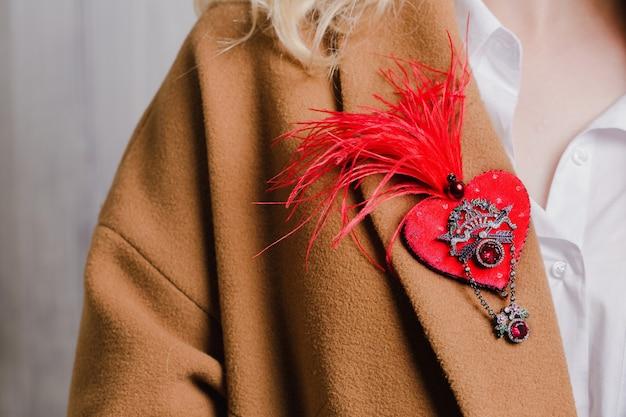 Czerwona broszka na kołnierzu płaszcza w kolorze wielbłąda