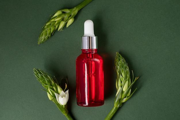 Czerwona butelka kosmetyków na ciemnozielonym tleulistnienie z białymi kwiatami wokół wygląda jak ramka