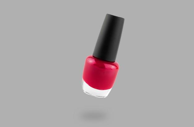 Czerwona butelka lakieru do paznokci na białym tle