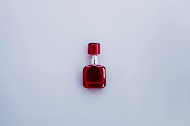 Czerwona butelka perfum na niebieskim tle. kosmetyki