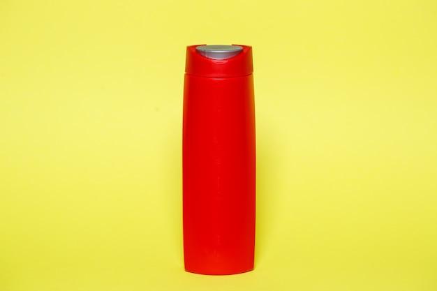 Czerwona butelka z żelowym szamponem lub mydłem w płynie na żółtym tle
