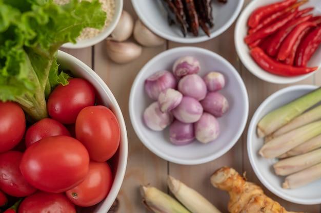 Czerwona cebula, cytryna, trawa cytrynowa, chilli, czosnek, galanga i sałata w filiżance na drewnianej podłodze.