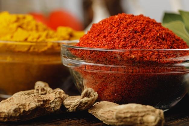 Czerwona chili pikantność w szklanym pucharze z ziele na zmroku stole