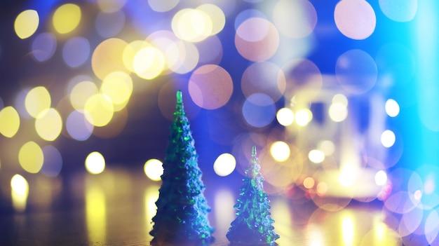 Czerwona choinka zabawka na gałęzi naturalnej jodły ze światłami girland w nieostrości w tle. metalowa zabawka z nacięciami na jelenie i płatkami śniegu. boże narodzenie, nowy rok, miejsce, bokeh.