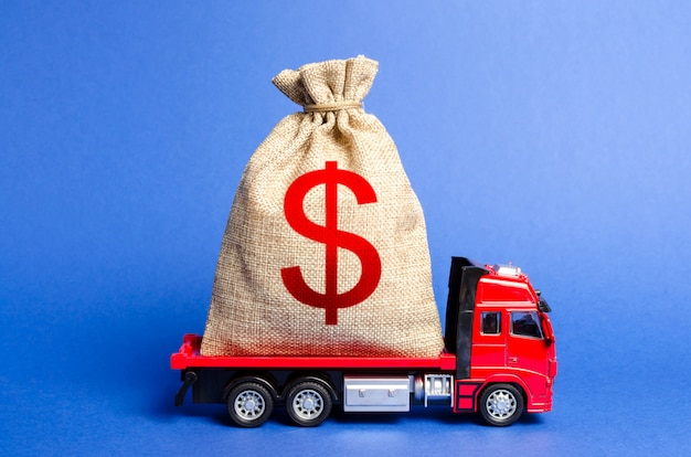Czerwona ciężarówka przewozi dużą torbę pieniędzy.
