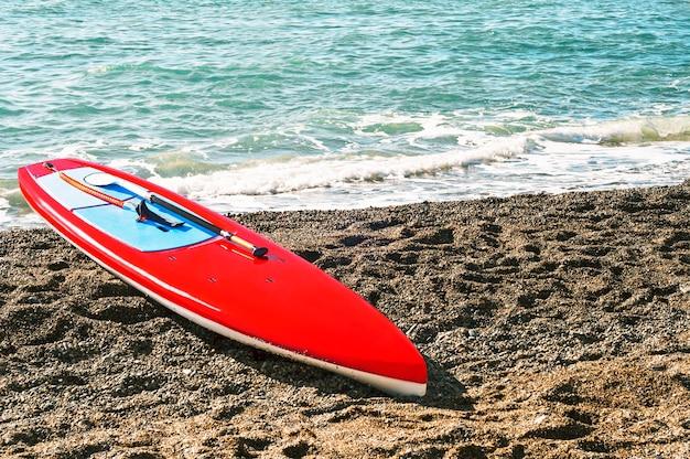 Czerwona deska do surfowania z wiosłem (sup) na plaży morskiej