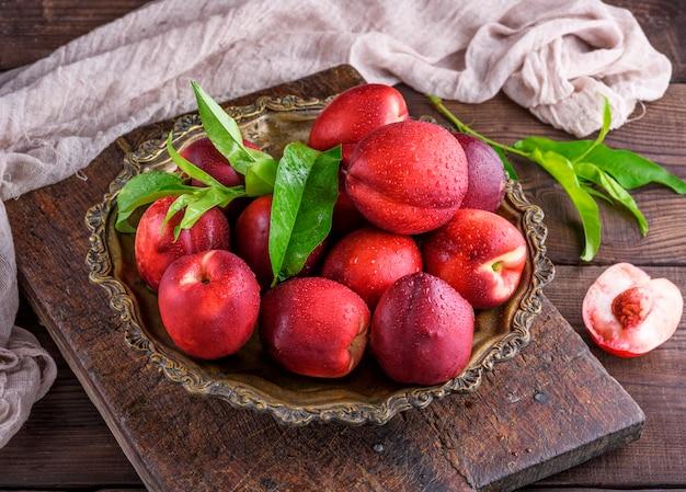 Czerwona dojrzała brzoskwini nektaryna w żelaznym talerzu