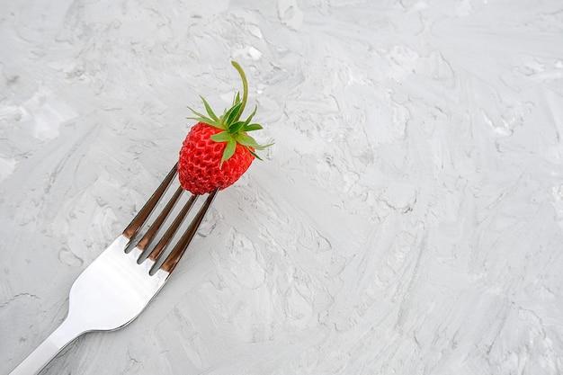 Czerwona dojrzała truskawka na rozwidleniu na tle szarość kamienia stół z kopii przestrzenią