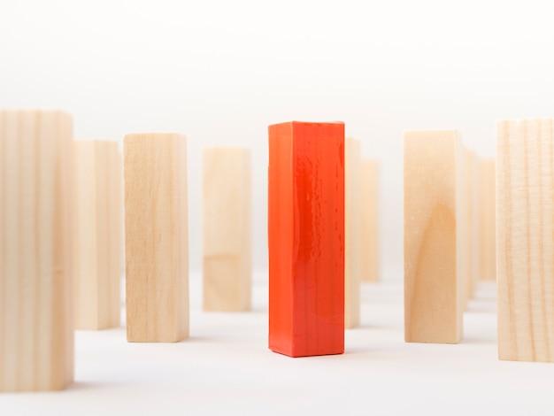Czerwona drewniana cegła otoczona normalnymi z bliska