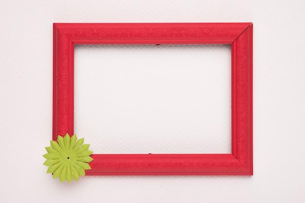 Czerwona drewniana granicy rama z zielonym kwiatem na biel ścianie