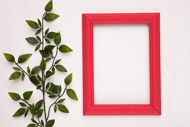 Czerwona drewniana ramka w pobliżu fałszywych zielonych roślin na białym tle