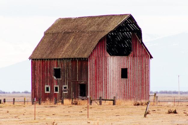 Czerwona drewniana stajnia w dużym polu