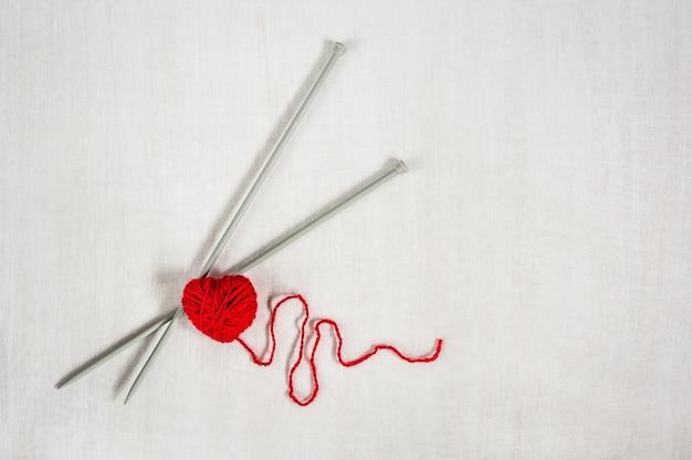 Czerwona dziewiarska przędza z igłami i bicie serca na białym drewnianym tle.