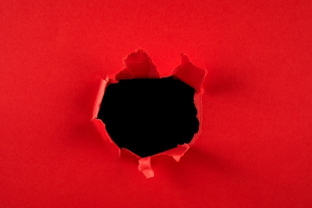 Czerwona dziura w papierze z podartymi bokami. boże narodzenie