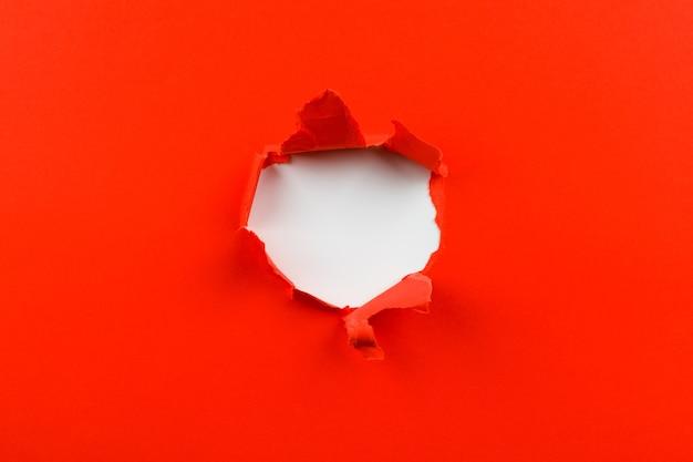 Czerwona dziura w papierze z podartymi bokami