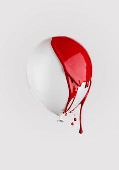 Czerwona farba kapie na biały balon. kreatywna modna minimalna koncepcja.