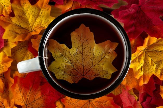Czerwona filiżanka herbaty na jesiennych liściach