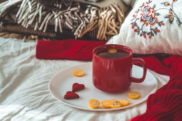 Czerwona filiżanka herbaty z kumkwatem i dwa ciasteczka serca na białym łóżku