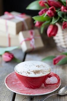 Czerwona filiżanka kawy, bukiet czerwonych kwiatów tulipanów i pudełka na prezenty