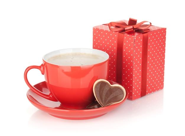 Czerwona filiżanka kawy, czekoladowe ciastko i pudełko upominkowe. na białym tle
