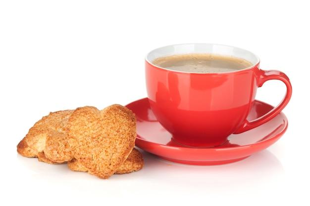 Czerwona filiżanka kawy i ciasteczka w kształcie serca. na białym tle