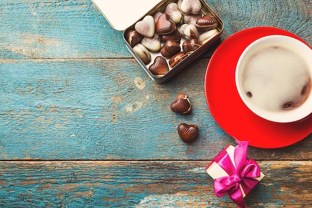 Czerwona filiżanka kawy i pudełko na niebieskim drewnianym stole. widok z góry. koncepcja walentynki.