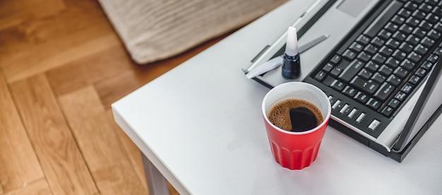 Czerwona filiżanka kawy, lakier do paznokci i laptopa tło