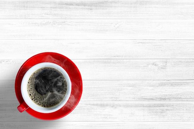 Czerwona filiżanka kawy na białym tle stołu z drewna lub drewniane tło, widok z góry, koncepcja na relaks