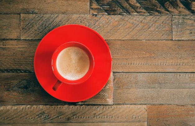 Czerwona filiżanka kawy na drewnianym stole. widok z góry