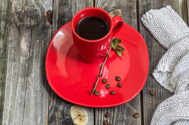 Czerwona filiżanka kawy na talerzu piękna drewniana ściana