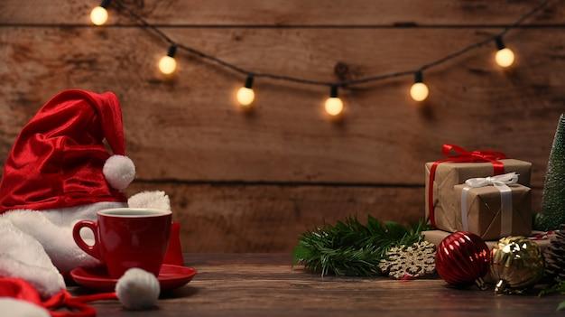 Czerwona filiżanka kawy, santa hat i świąteczne pudełka na drewnianym stole.