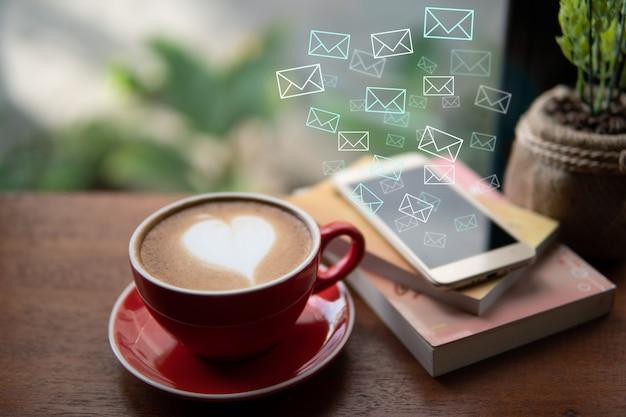Czerwona filiżanka kawy z latte art kierowym kształtem i poczta ikoną, kierowa ikona płynie z telefonu komórkowego, miękka ostrość projekt