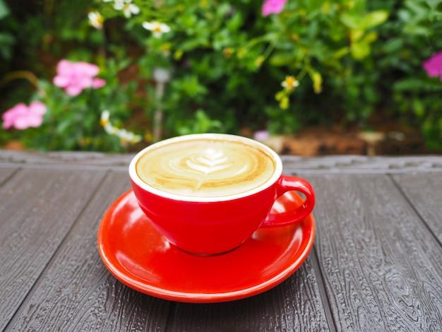 Czerwona filiżanka latte kawa na drewnianym stole w ogródzie.