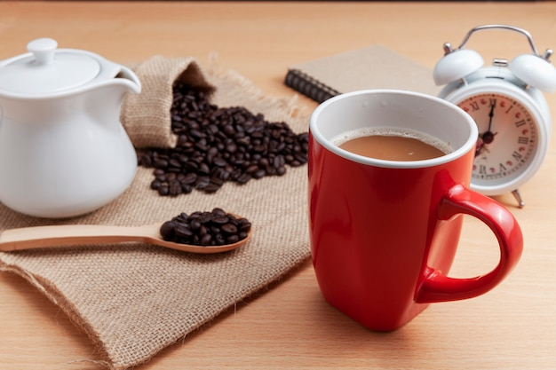 Czerwona filiżanka z kawowymi fasolami i białym budzikiem na biznesu stole