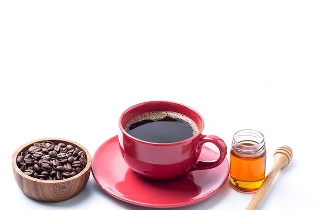 Czerwona filiżanki kawa i kawowa fasola w drewnianym pucharze, miód odizolowywający na bielu