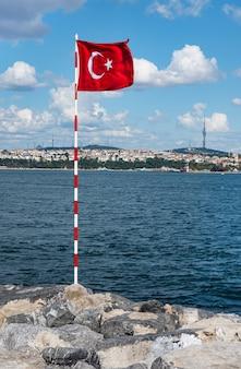 Czerwona flaga turecka stoi na kamiennym brzegu bosforu w słoneczny letni dzień. blokada w kraju z powodu pandemii koronawirusa. stambuł, turcja