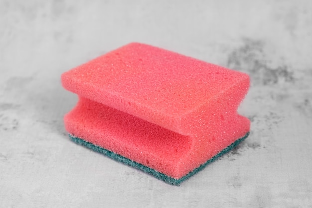 Czerwona gąbka do mycia naczyń na szarym tle. koncepcja usługi sprzątania, akcesoria do sprzątania.
