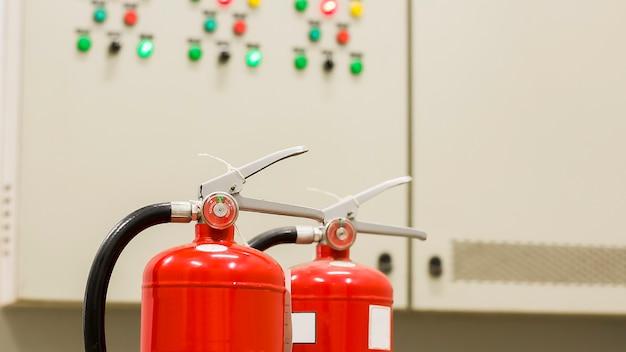 Czerwona gaśnica jest gotowa do użycia w przypadku pożaru w pomieszczeniu.
