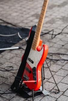 Czerwona gitara elektryczna na stojaku leży na ziemi