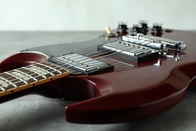 Czerwona gitara elektryczna na szarym teksturowanym stole