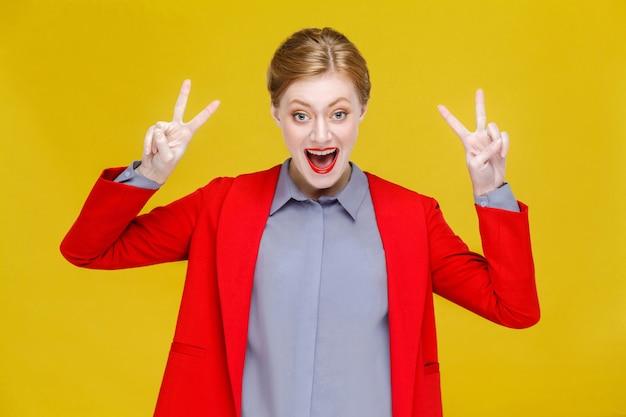 Czerwona głowa biznesowa kobieta w czerwonym garniturze pokazując znak v znak pokoju