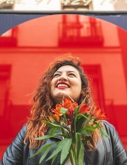 Czerwona głowa dziewczyna wącha kwiaty.