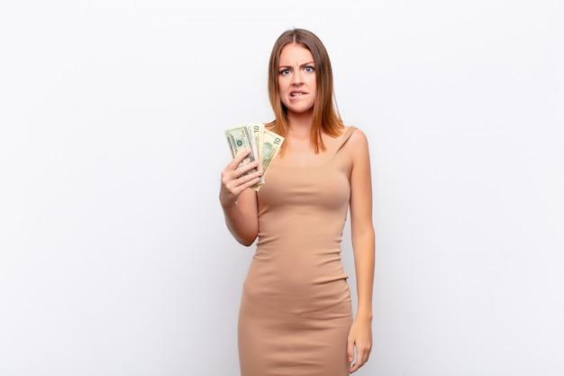 Czerwona głowa kobieta wyglądająca na zdziwioną i zdezorientowaną, przygryzając wargę nerwowym gestem, nie znając odpowiedzi na problem z banknotami dolarowymi