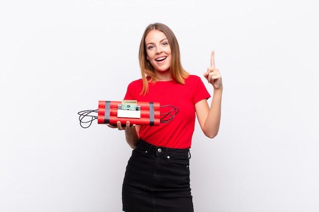 Czerwona głowa ładna kobieta czuje się jak szczęśliwy i podekscytowany geniusz po zrealizowaniu pomysłu, radośnie podnosząc palec, eureka! z bombą dynamitową