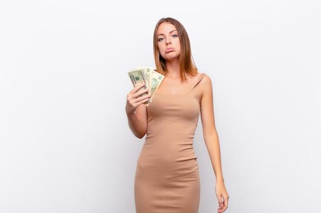 Czerwona głowa ładna kobieta czuje się smutna i płaczliwa z nieszczęśliwym spojrzeniem, płacze z negatywnym i sfrustrowanym nastawieniem z banknotów dolarowych