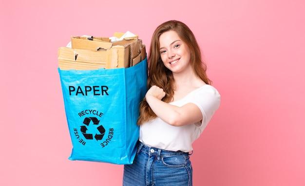 Czerwona głowa ładna kobieta czuje się szczęśliwa i staje przed wyzwaniem lub świętuje i trzyma papierową torbę z recyklingu
