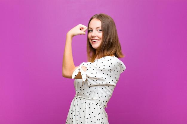 Czerwona głowa ładna kobieta czuje się szczęśliwa, zadowolona i silna, wyginając się i muskularny biceps, wyglądając mocno po siłowni na fioletowej ścianie