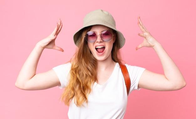 Czerwona głowa ładna kobieta turysta krzyczy z rękami w powietrzu